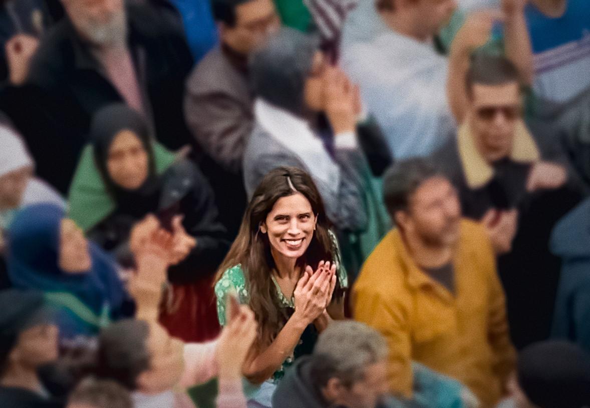 Imagem do poster do filme DNA. A imagem mostra a protagonista Neige, interpretada pela atriz Maïwenn, no meio de uma multidão, olhando para cima. Ela encara diretamente a câmera e sorri, com as mãos juntas em sinal de prece, e apenas ela está focada. A personagem de Maïwenn tem cabelos longos e lisos num tom de castanho médio e usa um vestido florido de fundo verde e mangas curtas.