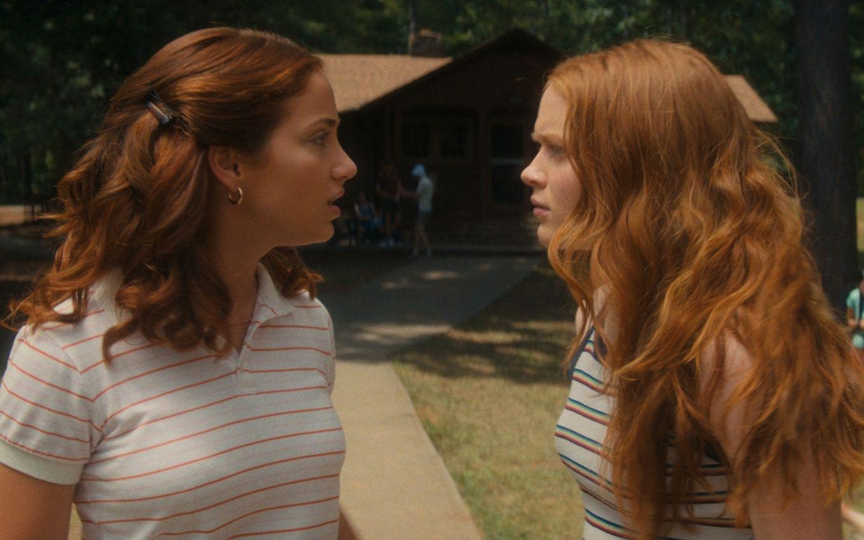 Cena do filme Rua do Medo: 1978. Emily Rudd e Sadie Sink se encaram, uma de frente para a outra e de perfil para nós. Emily, à esquerda, tem cabelos ruivos, é uma mulher branca e usa camisa polo branca com listras laranjas. Sadie, à direita, é mais jovem, também ruiva e branca, e usa uma blusa branca com listras vermelhas e azuis.