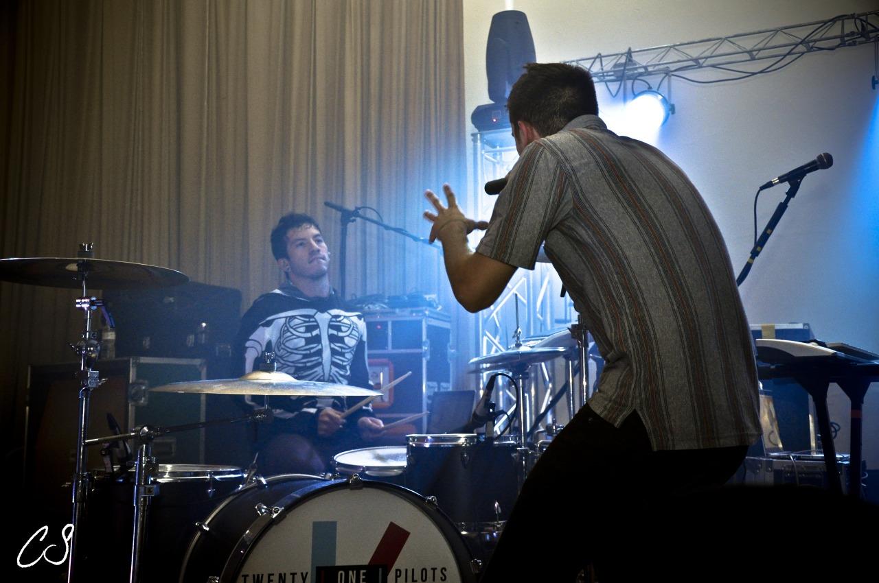 A imagem é uma foto de Tyler Joseph e Josh Dun em um show. Nela, Josh está na bateria, vestindo um moletom com estampa do corpo de um esqueleto. Ele é um homem branco, de cabelos castanhos escuros. Em sua frente, no lado direito, está Tyler, virado de costas e olhando para Josh. Ele está um pouco inclinado e segura um microfone na mão direita. Tyler é um homem branco, de cabelos castanhos escuros, ele veste uma camisa listrada e calça jeans.