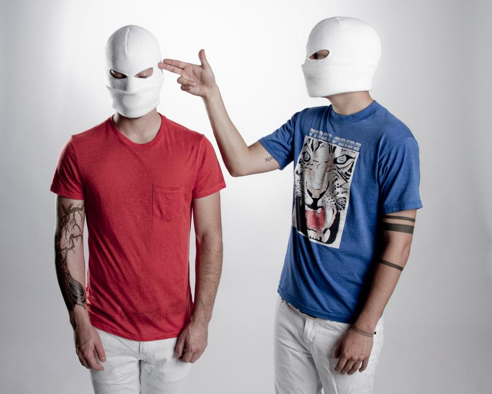 A imagem é uma foto de Tyler e Josh. Nela, Josh está ao lado esquerdo, em pé e com os braços ao longo do corpo, enquanto Tyler está do lado direito, com o corpo virado para josh, e a mão direita apontando para a cabeça de Josh fazendo sinal de arma. Josh é um homem branco, ele veste uma máscara de gorro branca, camiseta vermelha e calça branca; Tyler é um homem branco, ele veste uma máscara de gorro branca, camiseta azul com desenho de um tigre e calça branca.