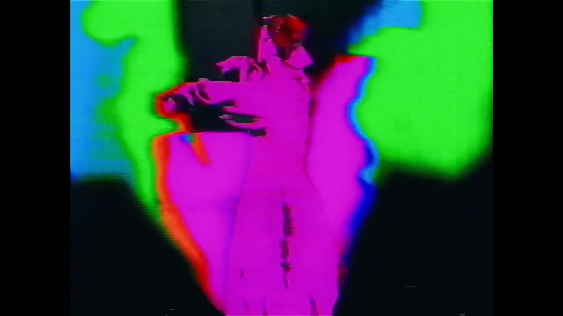 Cena do curta TV a Cabo (Ou Uma Noite na Vida). Perspectiva quadrada. Uma dançarina de costas para a tela, colorizada em um tom rosa choque, com tons azuis, verdes e vermelhos do seu lado e um negro acima e abaixo.