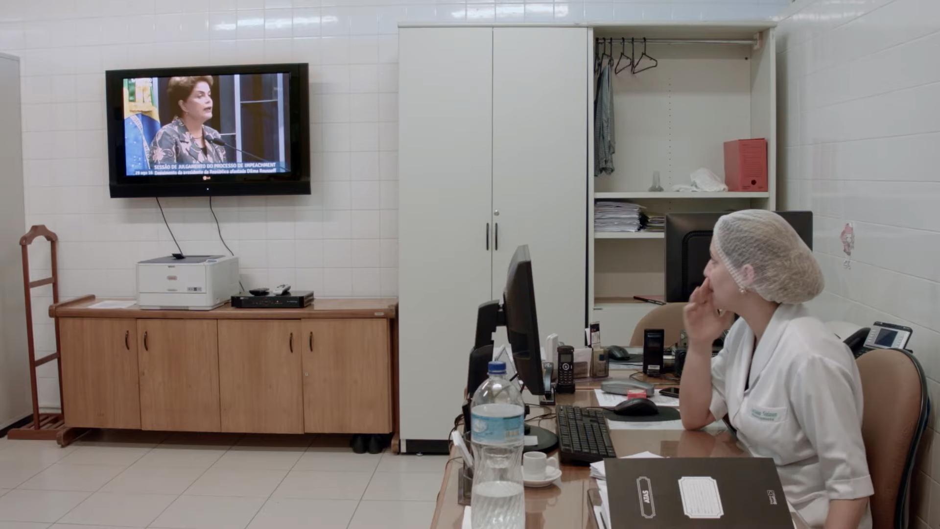 Cena do filme Alvorada. A imagem mostra uma sala do setor administrativo do Palácio da Alvorada. No lado direito da imagem, existe uma mesa de trabalho, com um computador, materiais de papelaria, um fichário e uma garrafa de água, onde uma mulher está sentada. Ela é branca, usa um jaleco branco e touca segurando os cabelos e assiste a TV ligada na parede no fundo da sala. A TV transmite o discurso de Dilma no Senado, no dia da votação de seu impeachment. Embaixo da TV, existe um armário baixo de madeira com quatro portas e ao lado um armário maior branco de duas portas.