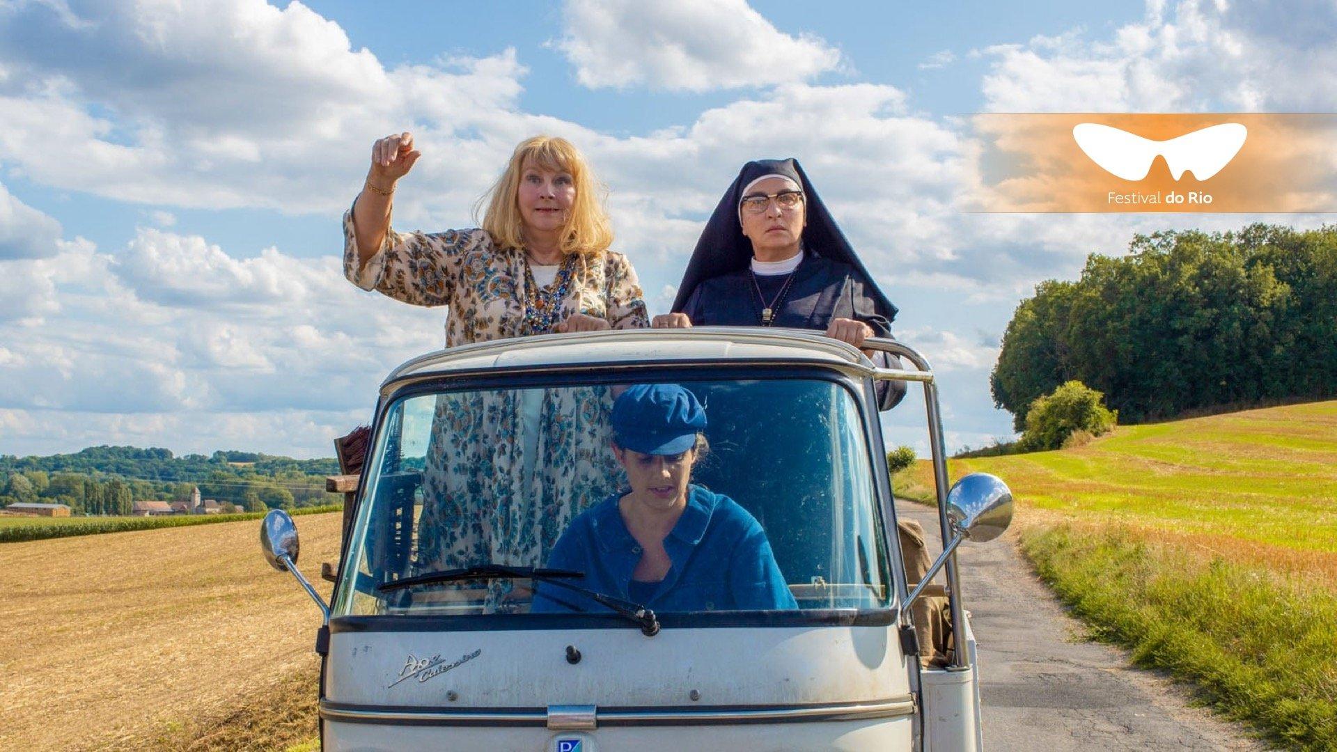 Cena do filme A Boa Esposa. Duas mulheres estão de pé na parte de trás de uma caminhão pequeno. A da direita usa trajes de freira e está com uma expressão séria. A da esquerda usa um vestido florido e está com um sorriso e as mãos levantadas.