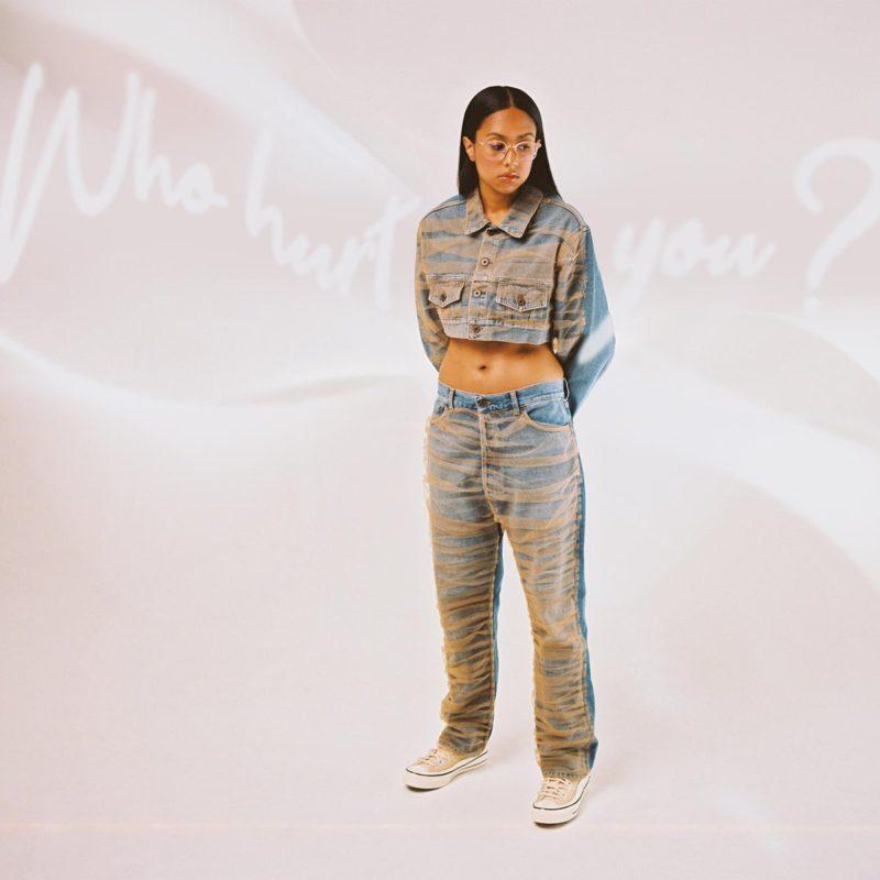 Capa do EP Who Hurt You?, da cantora Jensen McRae. A capa mostra ela, uma mulher jovem, negra, magra e de cabelos compridos, de pé e olhando para baixo.