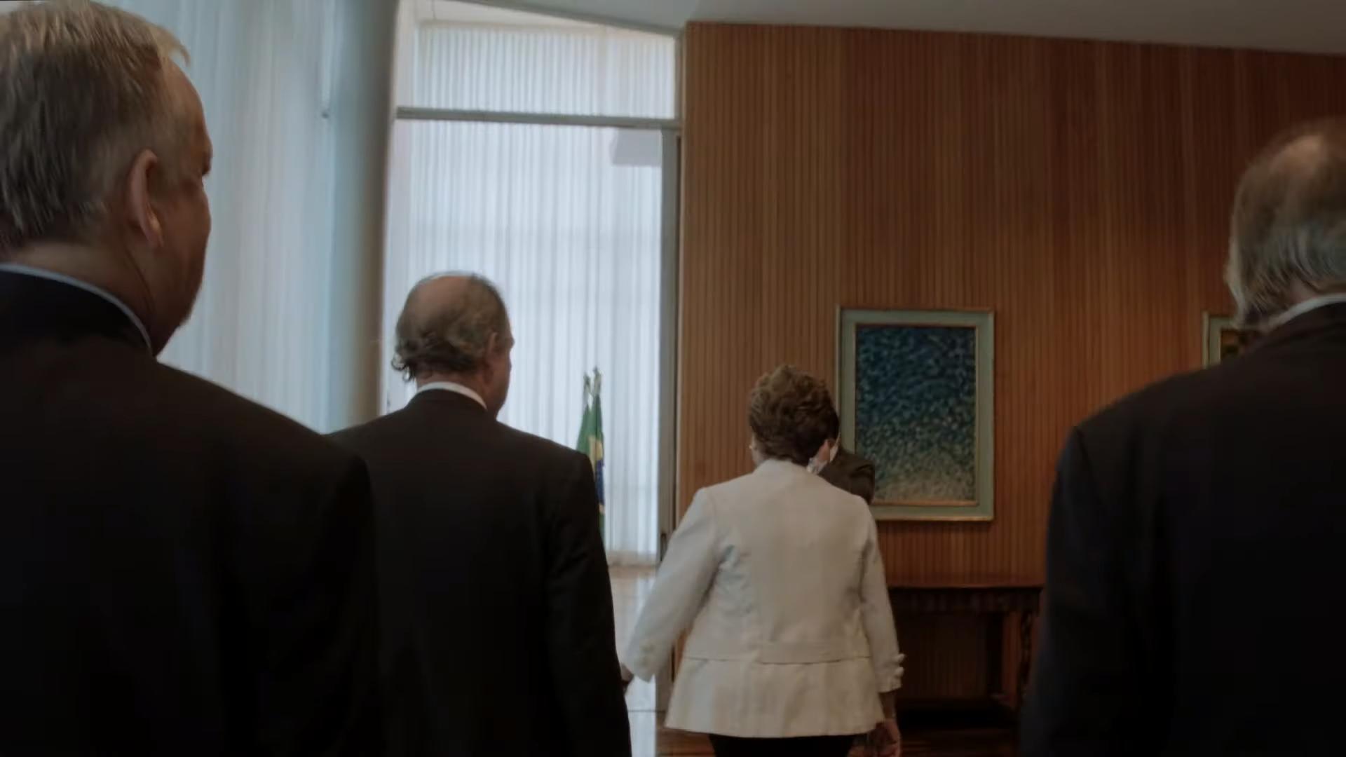 Cena do filme Alvorada. A imagem mostra a ex-presidenta Dilma Rousseff de costas, centralizada, e na frente de três homens. Dilma usa um blazer branco e caminha para a frente, e os homens que a seguem, todos brancos, vestem paletós pretos. Ela caminha em direção a uma sala com uma porta de vidro no lado esquerdo da imagem, e no lado direito, existe um painel de madeira ripado.