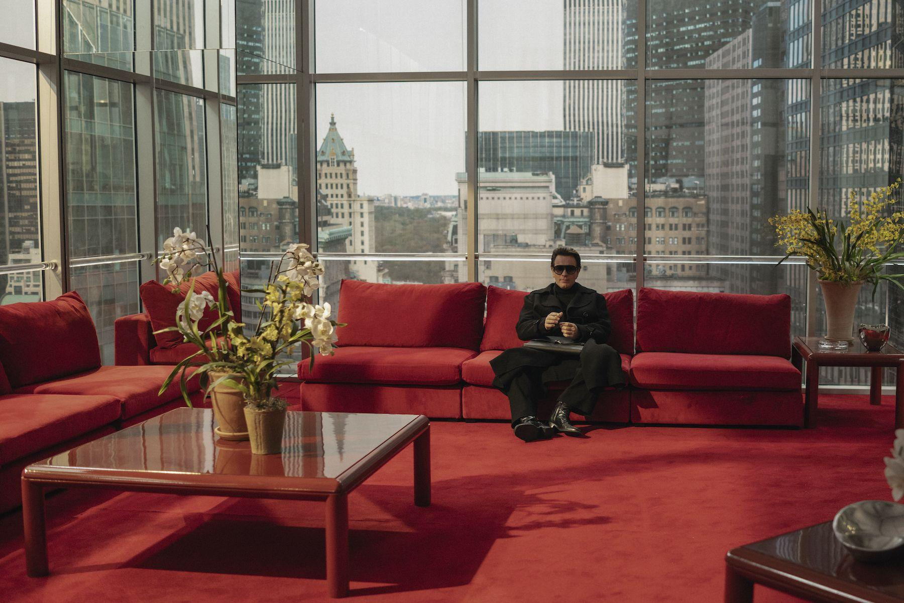 Cena da série Halston. Ewan McGregor está no fundo da imagem, vestido inteiramente de preto. Ele está sentado em um sofá vermelo, que combina com o carpete também vermelho da sala. Ao seu redor, todas as paredes são de vidro, assim como a mesinha no canto esquerdo, que contém um vaso com orquídeas.