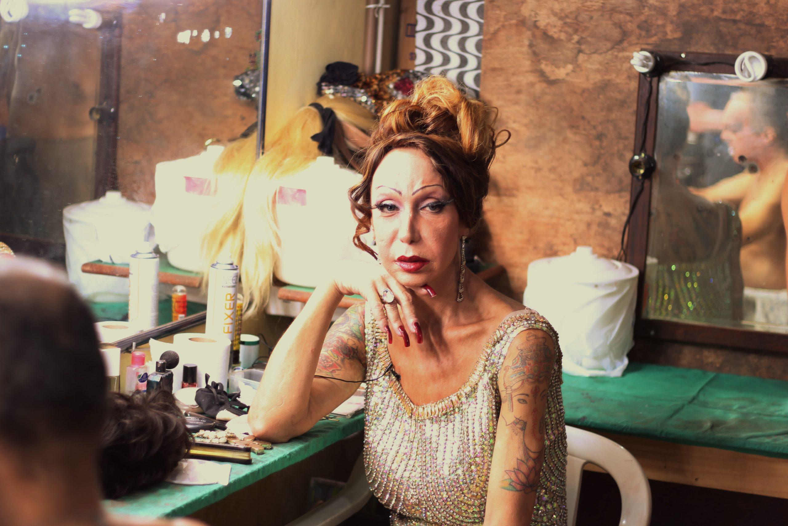 Cena do filme Luana Muniz - Filha da Lua. A foto mostra Luana sentada em seu camarim, maquiada, de vestido prateado e unhas vermelhas, olhando diretamente para a câmera. Ela tem a mão esquerda apoiando o rosto. Ao seu redor, vemos outras pessoas se preparando para o show.