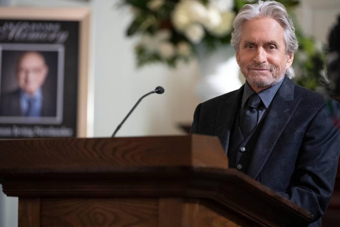 Cena da série O Método Kominsky. Nela, vemos Sandy, papel de Michael Douglas, frente a um púlpito, discursando no velório de Norman. Sandy é idoso, branco, tem um topete grisalho e usa terno preto. Ao fundo, vemos um cartaz com a foto de Norman.