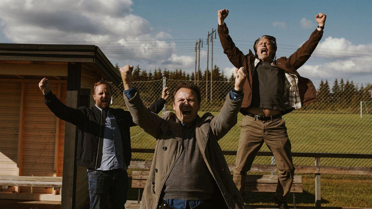 A imagem é uma cena do filme Druk - Mais uma Rodada. Nela estão, da esquerda para a direita, os personagens Nikolaj, interpretado por Magnus Millang, Peter, interpretado por Lars Ranthe, e Martin, interpretado por Mads Mikkelsen. Eles estão em frente a um campo de futebol, comemorando com os braços levantados para cima e os punhos cerrados. Nikolaj é um homem branco, de cabelos e barba castanhos, ele veste uma camisa azul claro, uma jaqueta escura e calça jeans. Peter é um homem branco, de cabelos castanhos, ele veste uma blusa e um casaco marrom e calça jeans. Martin é um homem branco, de cabelos grisalhos, ele está em cima de um banco e veste uma blusa e casaco marrons e calça marrom-claro.