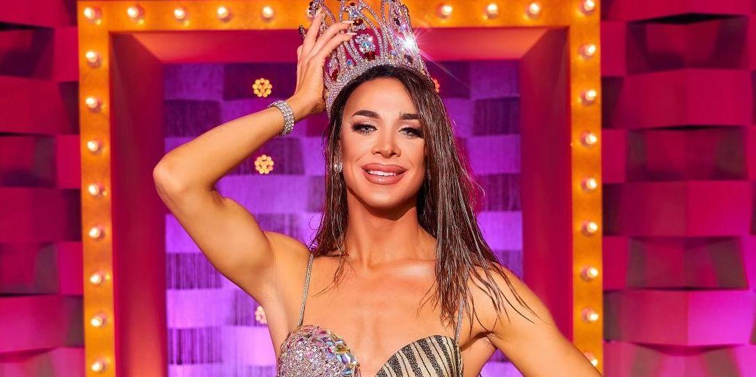 Cena de Drag Race España. Nela, vemos Carmen Farala com a coroa. Ela é uma drag queen branca, usa uma peruca castanha molhada e sorri, com a mão na cabeça, segurando a Coroa.
