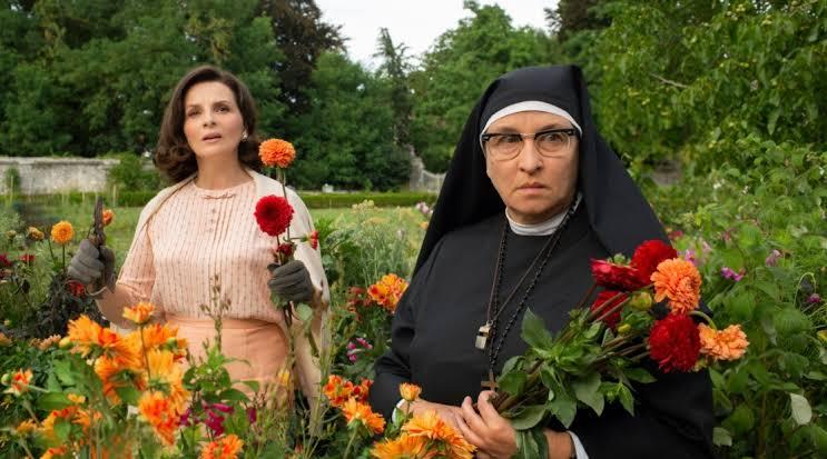 Cena do filme A Boa Esposa em que Paulette, uma mulher branca de cabelos castanhos curtos e roupa rosa claro, aparece segurando flores vermelhas e laranja. À esquerda está uma freira, que usa óculos e segura um buquê de flores. Os arredores da imagem está repleto de plantas e flores.