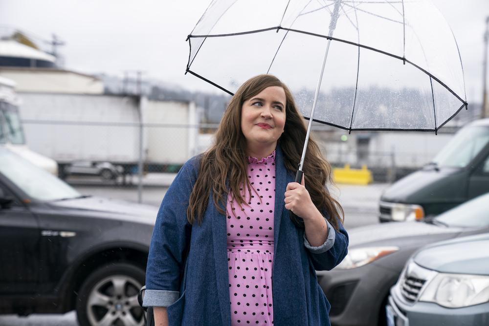 Cena da série Shrill. Na cena, vemos Aidy Bryant, uma mulher branca e gorda, parada na rua segurando um guarda-chuva de plástico transparente. Ela está com uma expressão feliz, usa uma blusa rosa e um casaco azul. Está de dia.