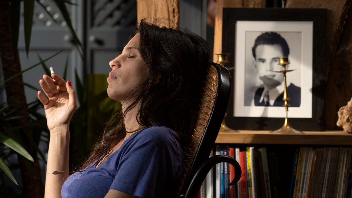 Cena do filme DNA. A foto mostra Neige de perfil, interpretada por Maiwenn, sentada numa poltrona com um cigarro na mão. Ela é franco-argelina, tem pele clara e cabelos escuros. Ela está de olhos fechados e a luz do sol inunda o ambiente.