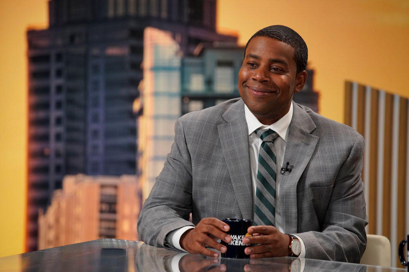 Cena da série Kenan. A cena mostra Kenan Thompson, um homem adulto, negro e de cabelo curto, sentado em uma bancada de programa de TV, sorrindo, usando terno cinza e segurando uma caneca preta com as duas mãos em cima da mesa.