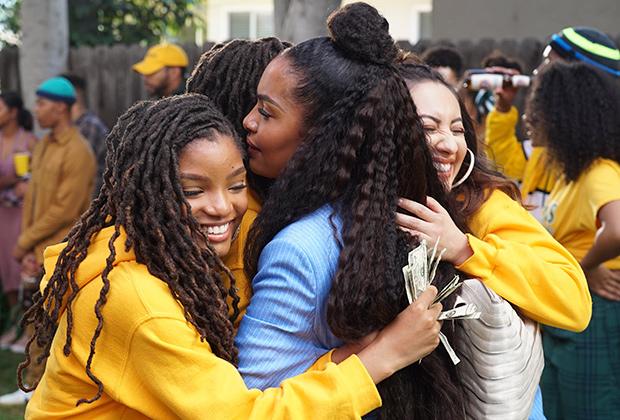 Cena de grown-ish. Nela está uma menina negra, de cabelos cacheados longos com uma parte presa em um coque, sendo abraçada por outras três meninas, duas negras e uma branca, todas usando um moletom amarelo. As meninas sorriem. No fundo é possível ver pessoas espalhadas por um jardim.