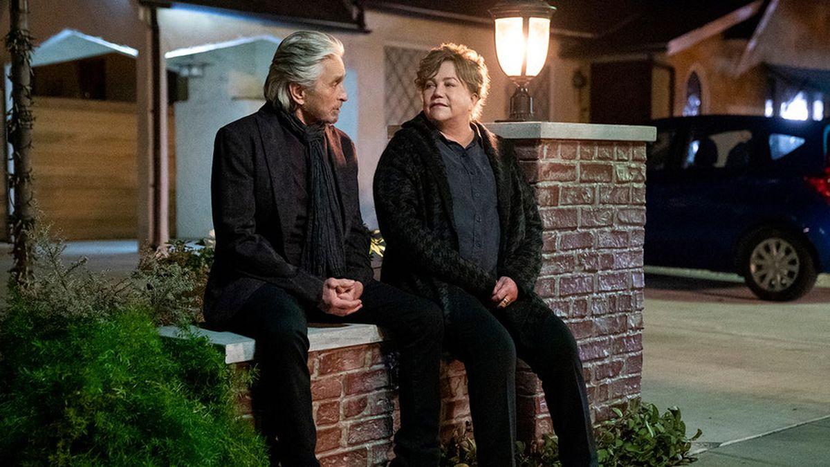 Cena da série O Método Kominsky. Nela, vemos Sandy e Roz sentados em uma mureta na rua, à noite. Eles são idosos, brancos e se olham nos olhos.