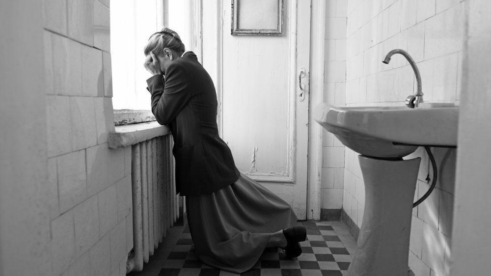 Cena do filme Caros Camaradas! Trabalhadores em Luta. A fotografia é em preto-e-branco e mostra uma mulher ajoelhada no chão de um banheiro. Ela usa saia comprida, um casaco escuro e o cabelo está preso em um penteado. Suas mãos cobrem o rosto e ela as apoia no batente da janela. Podemos ver, ao seu lado, uma pia.
