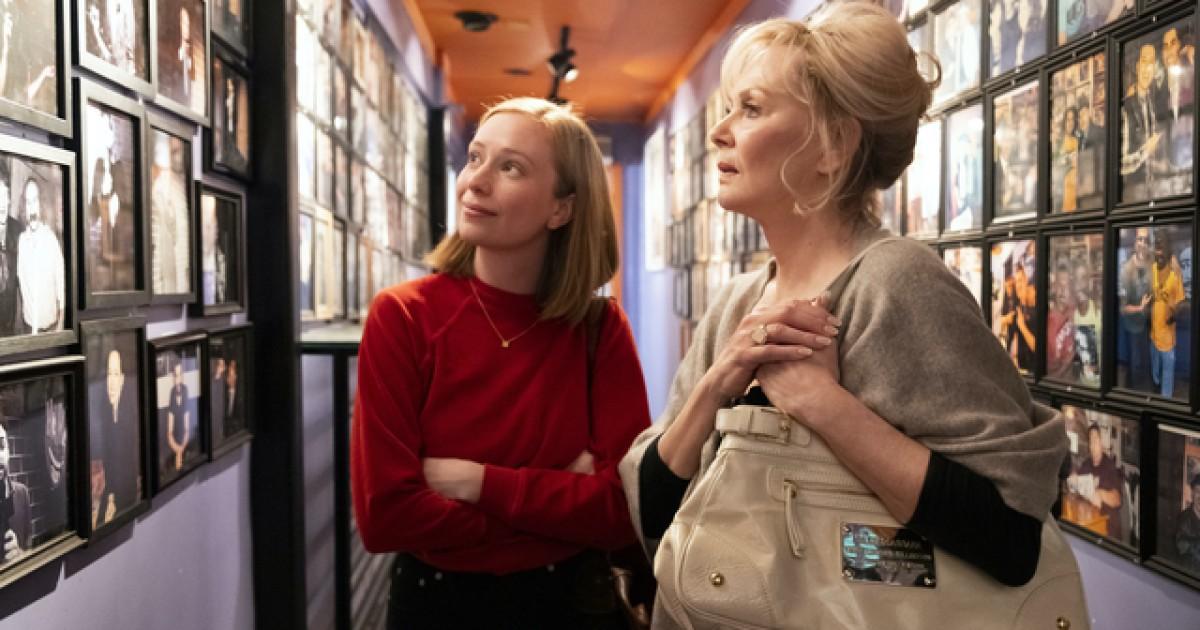 Cena da série Hacks. A cena mostra Deborah e Ava olhando para uma parede de fotos, no corredor de um bar. Deborah é uma mulher branca, loira e idosa, ela veste uma blusa cinza e segura a bolsa bege rente ao corpo. Ava é uma mulher branca, jovem e loira, que está de braços cruzados olhando para a parede de fotos, usando um suéter vermelho.