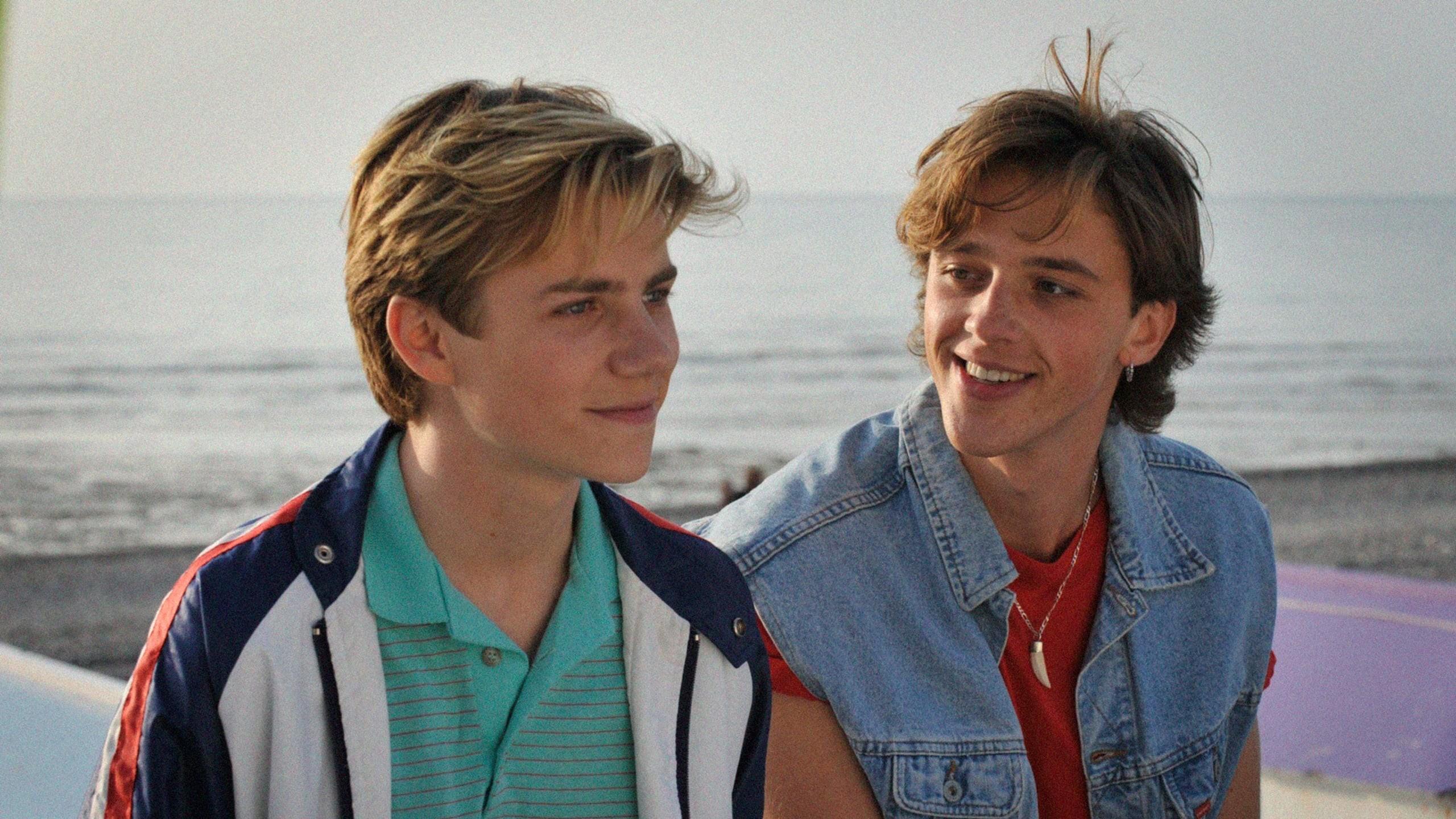 Cena do filme Verão de 85. Nela, dois adolescentes brancos estão sentados no píer da praia, está de dia, e o mar azul aparece atrás deles. Eles sorriem um para o outro.