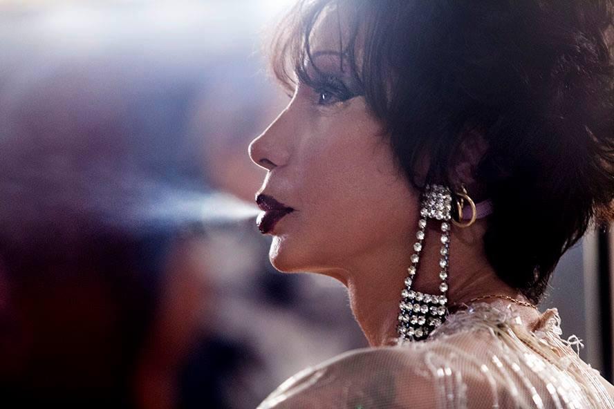 Cena do filme Luana Muniz - Filha da Lua. A foto mostra Luana de perfil. Ela usa peruca preta, bem curta, e solta fumaça do cigarro pela boca. Ela usa batom vermelho, cílios postiços e brincos enormes, cheios de strass.