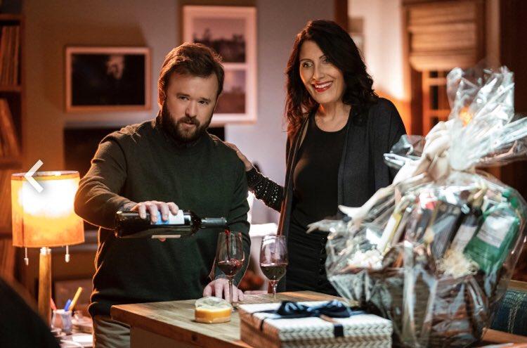 Cena da série O Método Kominsky. Nela, vemos os atores Haley Joel Osment e Lisa Edelstein sorrindo, com taças de vinho na mesa em sua frente. Eles são brancos, tem cabelos pretos e usam roupas escuras.