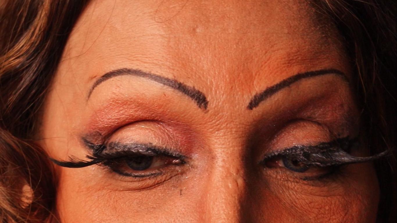 Cena do filme Luana Muniz - Filha da Lua. A foto mostra Luana em um close dos olhos. Vemos sua testa, e as sobrancelhas desenhadas, além dos olhos olhando para uma direção diferente da câmera. Ela usa rímel e cílios postiços.