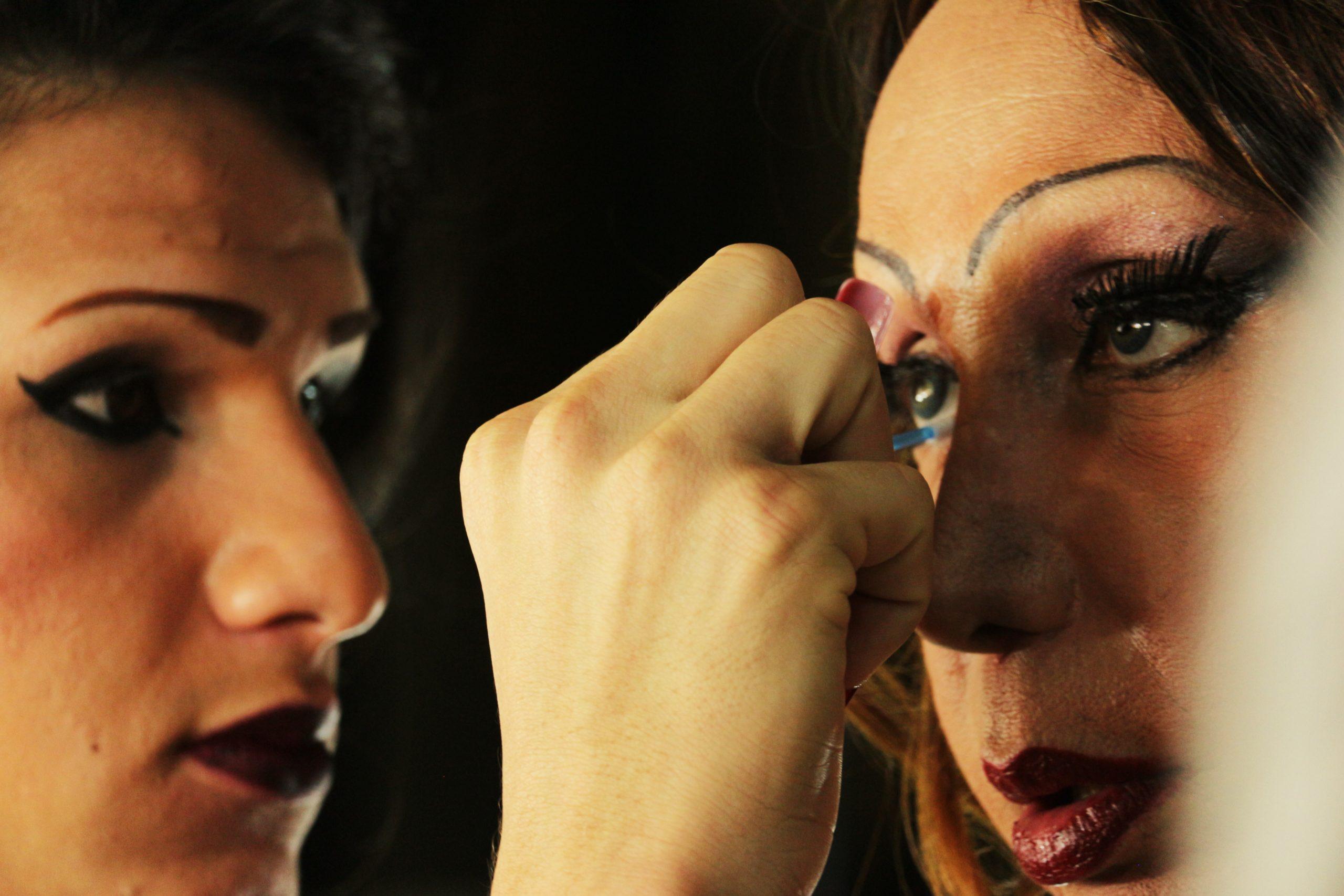 Cena do filme Luana Muniz - Filha da Lua. A foto mostra uma mulher colocando maquiagem nos olhos de Luana. As duas pessoas são brancas, e usam batom vermelho. Luana está em foco, olhando para frente, enquanto a outra mulher está concentrada no olho esquerdo da artista.