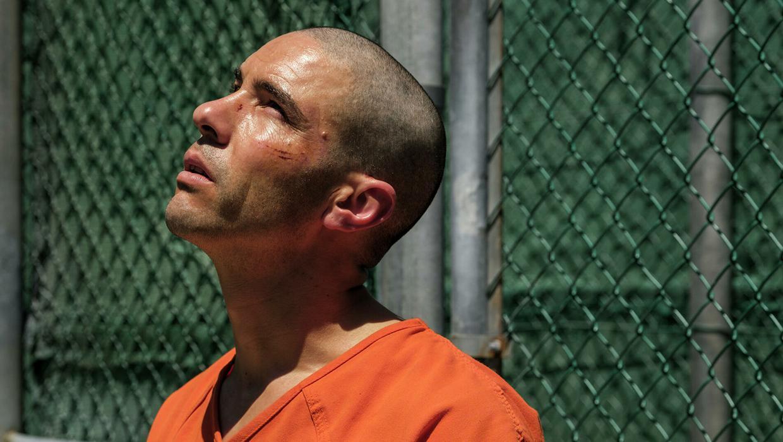 A imagem é uma cena do filme O Mauritano. Nela, está o personagem Mohamedou Ould Slahi, interpretado por Tahar Rahim. Ele é um homem branco, com o cabelo raspado, e veste um uniforme laranja de presidiário. Mohamedou está na parte externa de um presídio, olhando para cima, ele tem ferimentos leves no seu rosto.