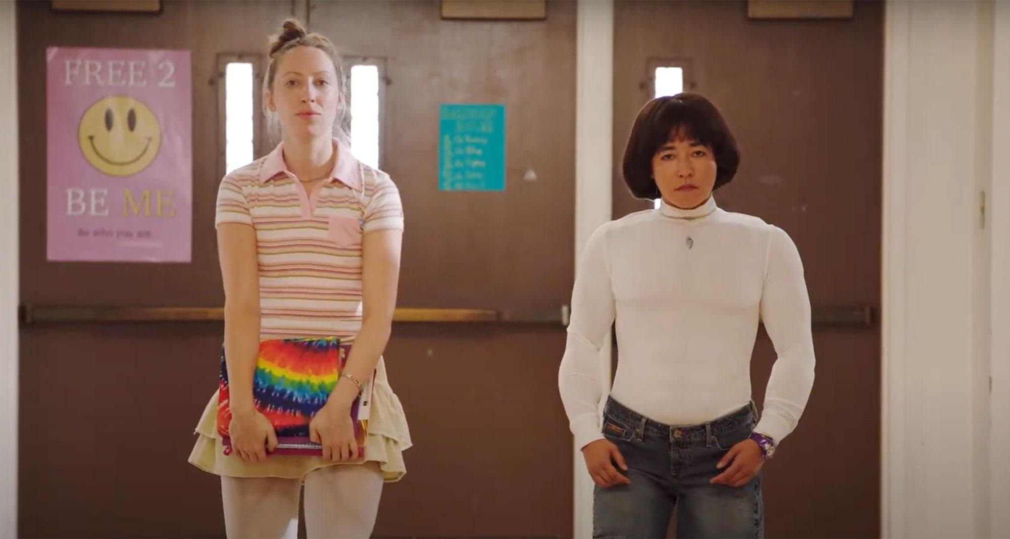 Cena da série Pen15. Vemos duas mulheres adultas andando pelo corredor de uma escola. A da direita é asiática, tem cabelo preto com corte tigelinha, usa uma camisa branca com enchimento para parecer que está musculosa e veste uma calça jeans. A mulher da esquerda é branca, loira com cabelo longo preso num coque, veste uma camiseta listrada e usa uma saia amarela. Ela carrega seu material escolar nas mãos.