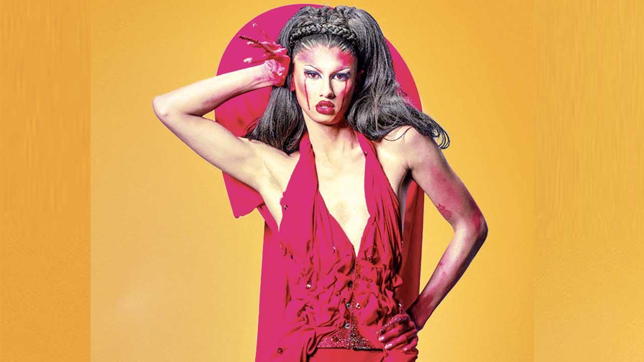 Cena de Drag Race España. Nela, vemos a drag queen Inti, pessoa não-binária de origem boliviana, que tem a pele clara e usa peruca preta, roupa vermelha e segura a mão atrás da cabeça, posando em frente a um fundo laranja.