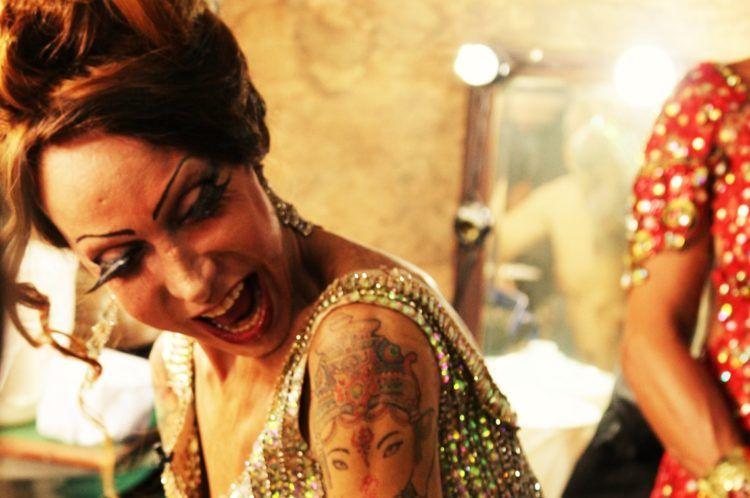 Cena do filme Luana Muniz - Filha da Lua. A foto mostra Luana dentro do camarim, rindo. Vemos sua boca aberta, feliz, e uma tatuagem no braço direito. Ao seu lado, alguém está cortado da imagem.