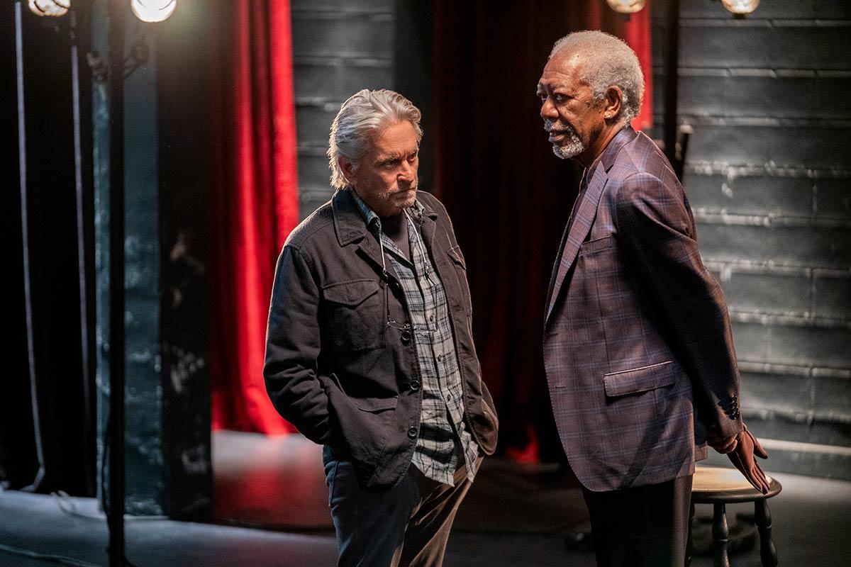 Cena da série O Método Kominsky. Nela, vemos Sandy e Morgan Freeman de pé, se olhando. Sandy é idoso, branco, usa camisa xadrez e está com as mãos nos bolsos da calça. Freeman é idoso, negro e está com as mãos nas costas.