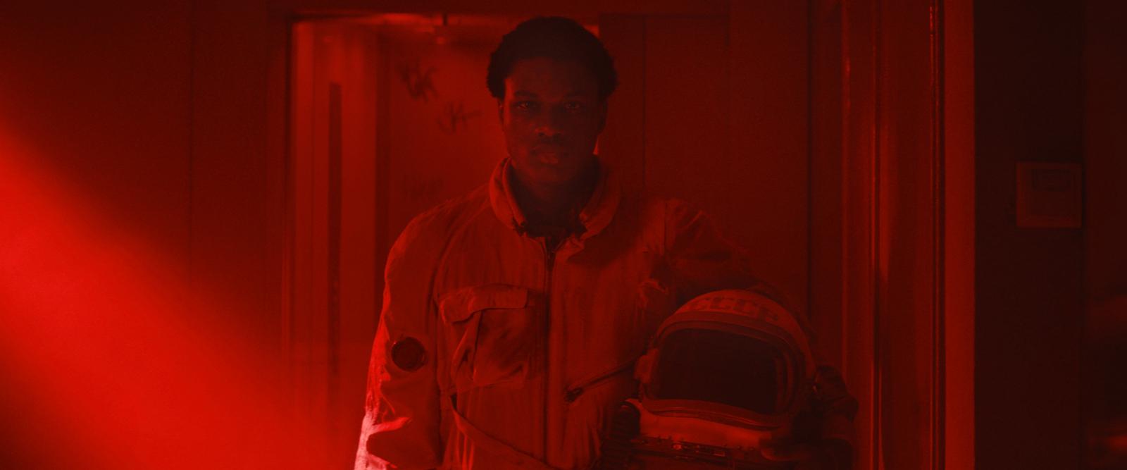 Cena do filme Edifício Gagarine. O personagem Youri, um menino de 16 anos negro de pele escura, está vestido com uma roupa de astronauta vintage. Ele segura o capacete da roupa nos braços. Ele está em um corredor, caminhando em direção a câmera. A iluminação da cena é toda em vermelho.