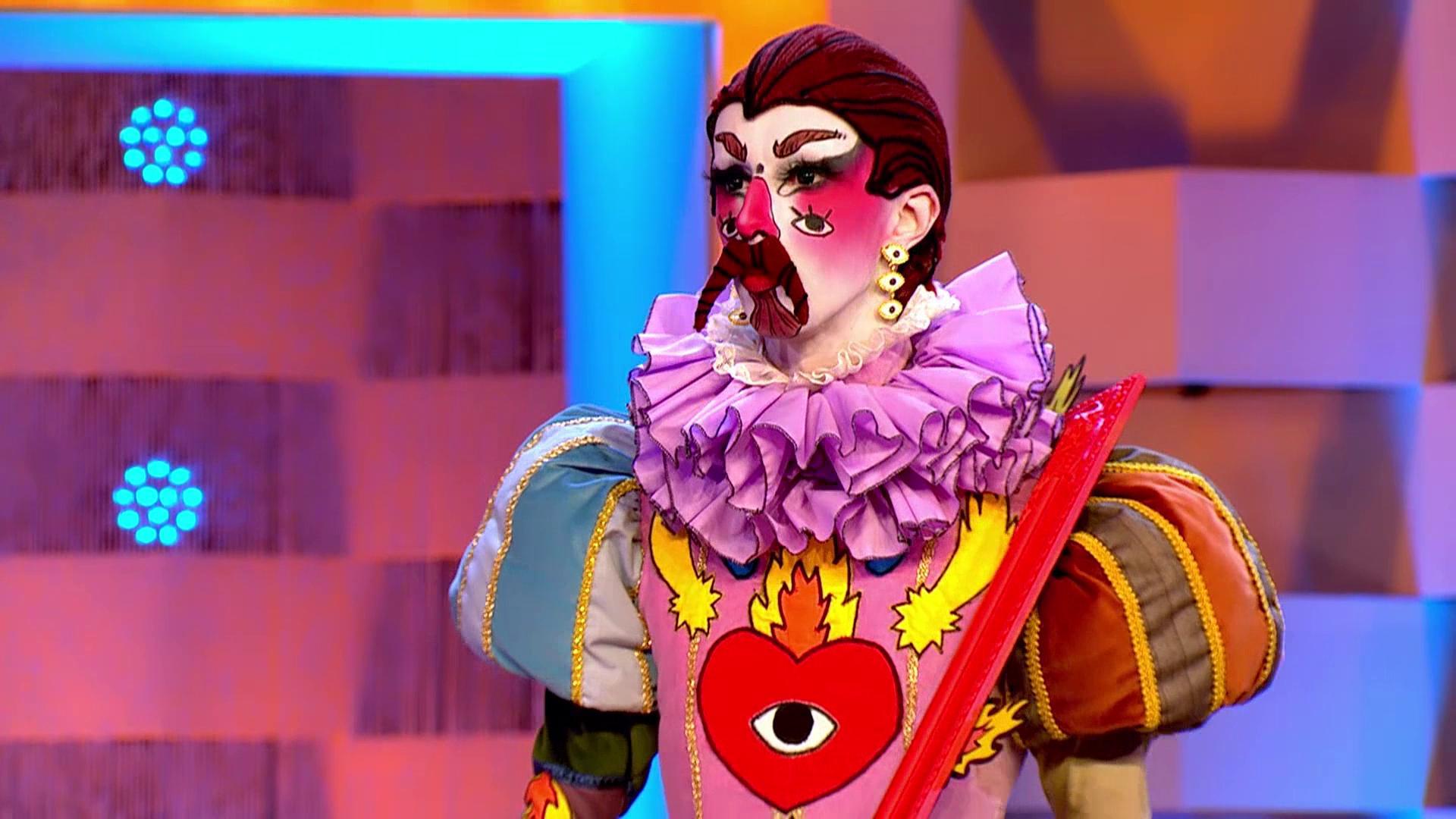 Cena de Drag Race España. Nela, vemos a drag queen Hugáceo Crujiente. Ela usa maquiagem no rosto, pintado de branco, com desenhos coloridos. Podemos ver o desenho de olhos em suas bochechas e em um encarte de coração em seu peito.