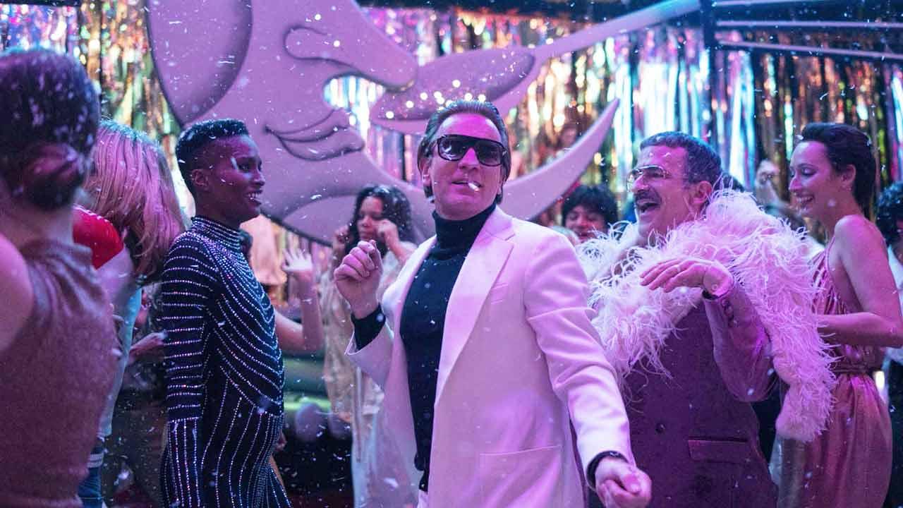 Cena da série Halston. Ewan McGregor está no centro, de paletó branco e camisa preta de gola alta. Ele tem um cigarro na boca, usa óculos escuros e está em uma posição dançante. Ao seu redor, outras pessoas também se divertem.