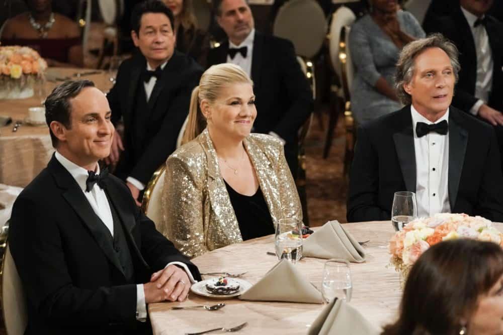 Cena da série Mom, que mostra 3 pessoas brancas sentada à uma mesa chique, usando roupas de gala e olhando para um palco.