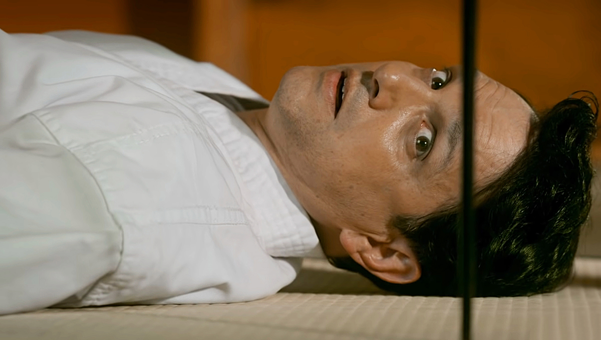 Cena do seriado Cobra Kai. Ralph Macchio está deitado, do peito à cabeça, em um tapete bege listrado. Ele é um homem de 60 anos, com cabelos curtos pretos, olhos castanhos esverdeados e barba aparada. Ele veste um kimono branco e está com expressão assustada, olhando para algo fino e comprido preso ao chão, do seu lado. O fundo de trás está borrado.