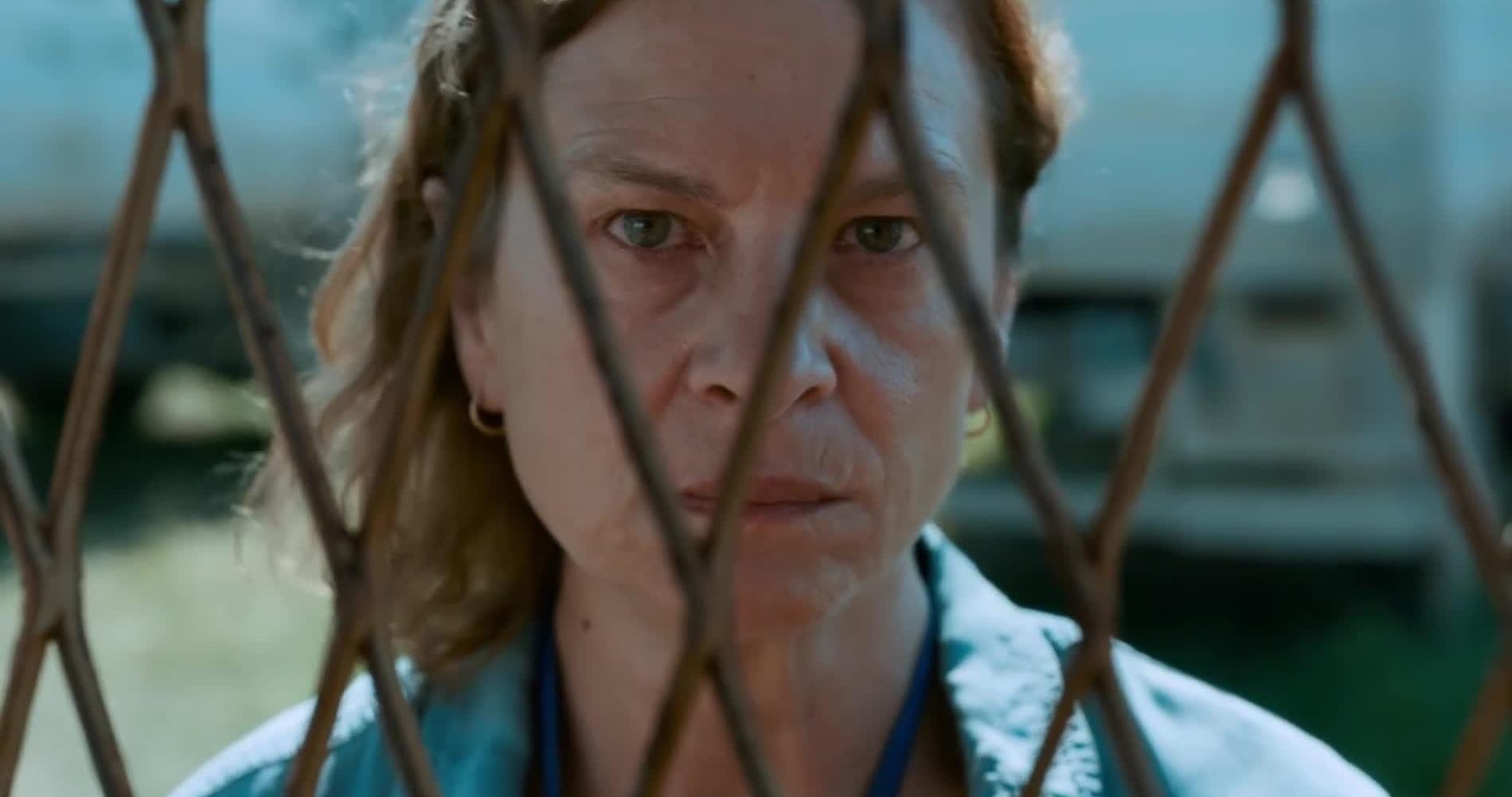 Cena do filme Quo Vadis, Aida?. Ao centro da imagem, vemos Aida, uma mulher branca aparentando ter cerca de 60 anos, de cabelos loiros escuros na altura do ombro e olhos verdes, encarando a câmera por trás de grades.