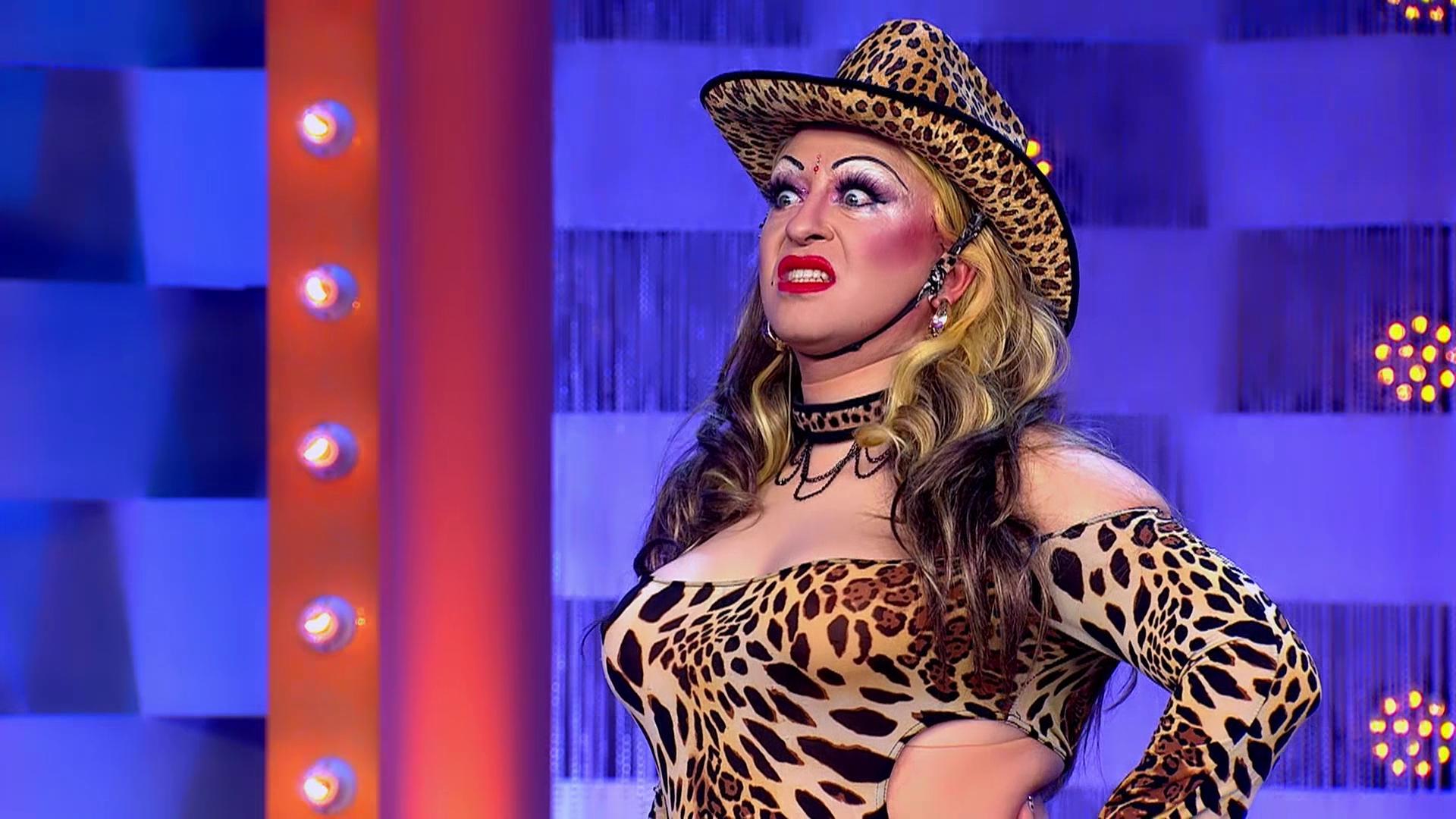 Cena de Drag Race España. Nela, vemos Pupi Poisson. Ela é uma drag queen branca, gorda e baixa. Usa peruca loira, chapéu de cowboy e roupa de estampa de oncinha. Ela faz cara de brava, mostrando os dentes.