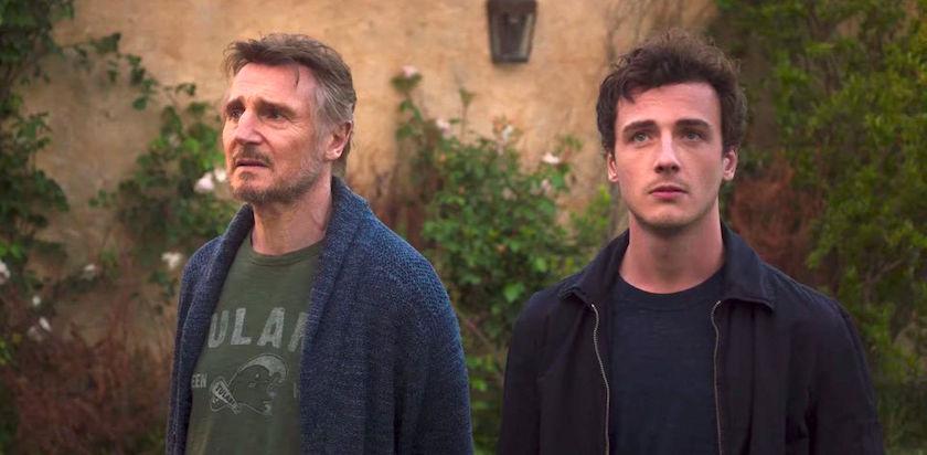 Cena do filme De volta à Itália. Na foto, o ator Liam Neeson veste blusa de lã azul e uma camiseta verde, possui cabelos grisalhos e barba; ao seu lado Micheál Richardson veste uma jaqueta preta e camiseta azul escura. Ambos são homens brancos. Ao fundo há uma parede de cor laranja desbotada com algumas plantas verdes.