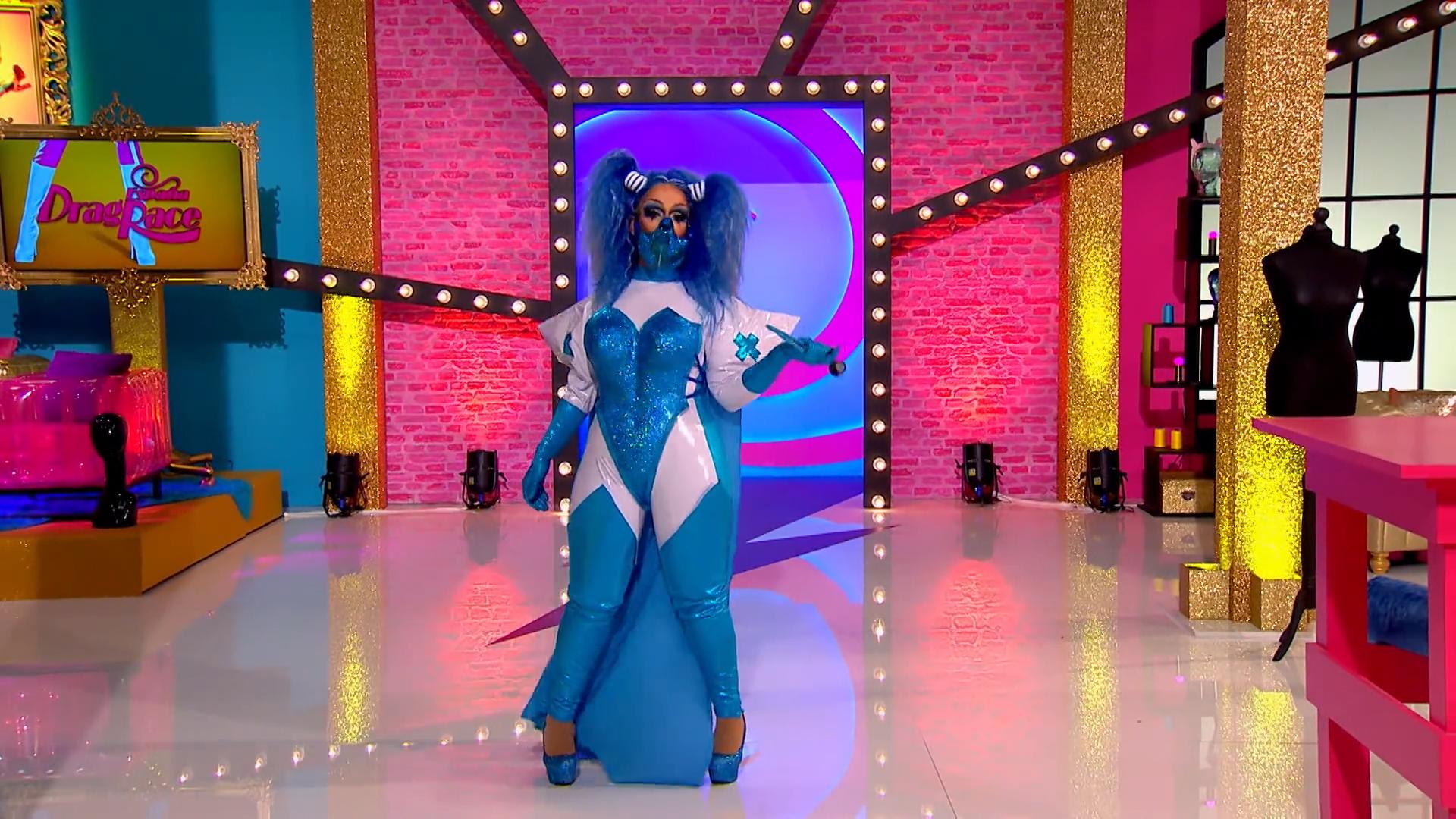 Cena de Drag Race España. Nela, vemos a drag queen Killer Queen. Ela é branca, usa roupa azul e uma peruca da mesma cor. Ela posa no Ateliê, com uma mão solta e a outra rente ao corpo.