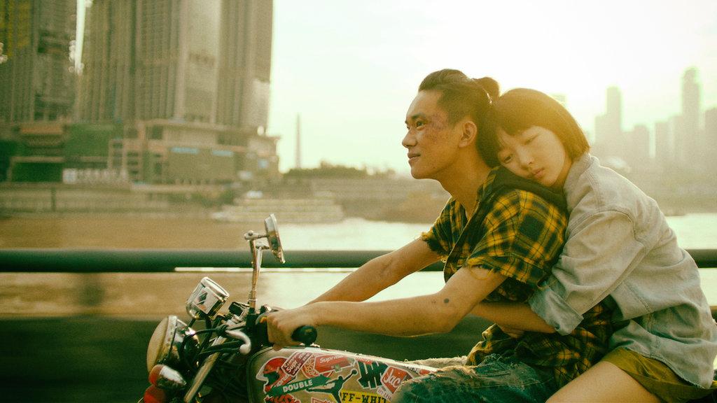 Cena do filme Dias Melhores. Fotografia em modo paisagem com tom amarelo saturado. No lado direito da imagem estão Xiao Bei e Chen Nian, interpretados por Dongyu Zhou e Jackson Yee, em ordem. Ambos estão sobre uma motocicleta em uma ponte. Xiao Bei é um rapaz amarelo, com topete amarrado em rabo e camisa xadrez amarela. Ele conduz a motocicleta e está machucado no rosto e braços. Atrás dele está Chen Nian, que o abraça e encosta sua cabeça no ombro dele. Ela é uma garota amarela de cabelo preto curto e franja, vestindo uma camisa jeans. Atrás de ambos está um canal e prédios altos da cidade de Hong Kong.