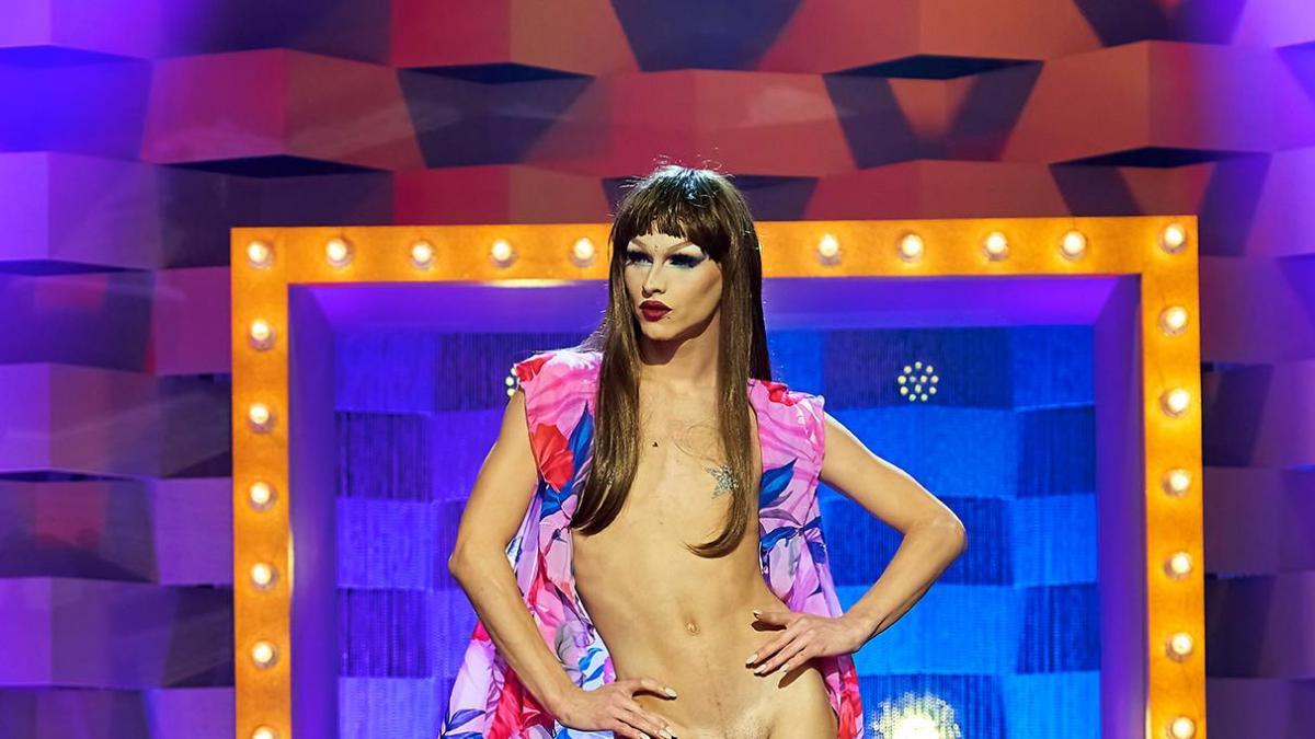 Cena de Drag Race España. Nela, vemos a drag queen Sagittaria na passarela. Ela é branca, está sem camisa e usa peruca alisada e longa.