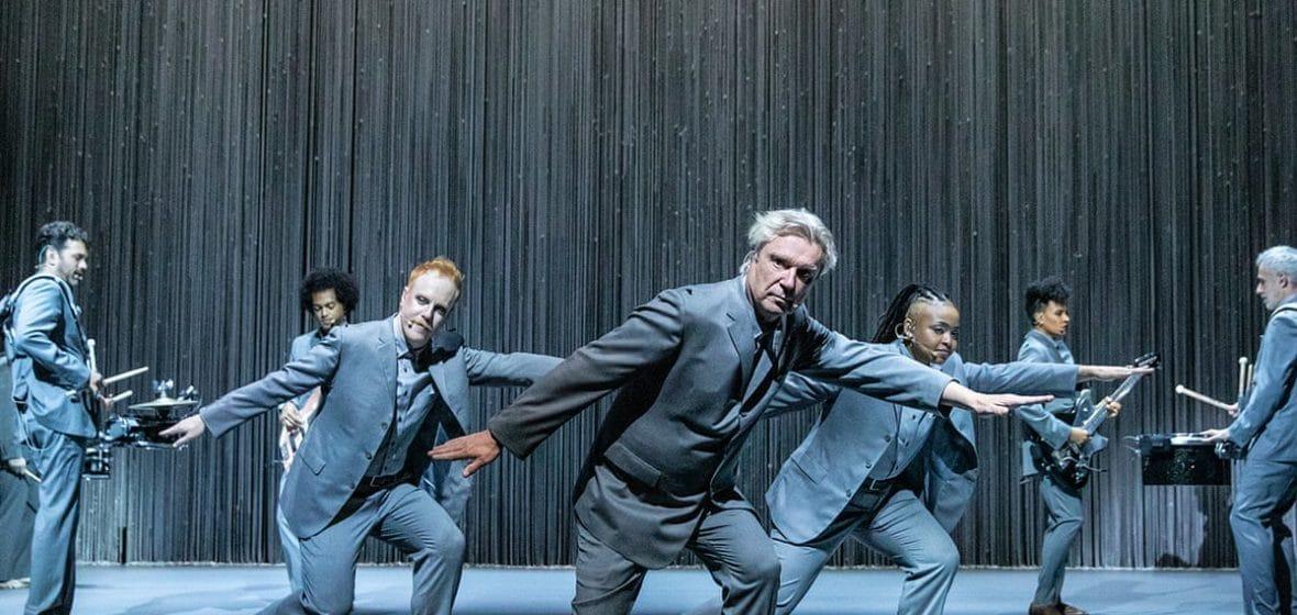 Cena do filme American Utopia. Vemos sete pessoas, homens e mulheres, num palco azul vazio com uma cortina no fundo. Todos vestem ternos do mesmo tom de azul. As três pessoas à frente estão com os braços e pernas inclinados, como se estivessem surfando. Atrás dos três, os outros quatro tocam seus respectivos instrumentos.