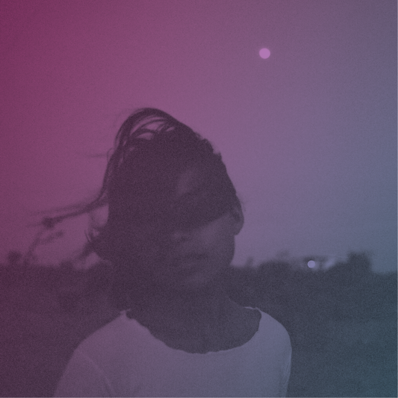 Capa do álbum Nightshade. Fotografia quadrada. Uma mulher ocupa o meio da imagem. Ela veste uma roupa clara, provavelmente branca, e tem o rosto coberto pelo próprio cabelo. Ao fundo, uma possível vegetação aparece embaçada. Um filtro roxo foi aplicado na fotografia inteira.