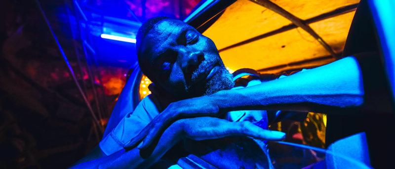 Cena do filme Ar Condicionado. Mostra de perto um homem negro de olhos fechados, cabelo curto e barba grisalha com os dois braços apoiados através da janela aberta de um carro. Ele é banhado por uma luz azul. O teto do carro é iluminado por uma luz amarela.