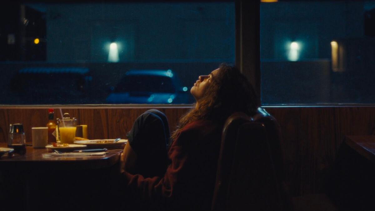 Cena de Part 1: Rue, o Episódio Especial de Euphoria. A imagem mostra a protagonista Rue sentada à mesa de uma lanchonete num bando estofado, de perfil, durante a noite. Rue é interpretada por Zendaya, uma jovem negra de cabelos castanhos cacheados volumosos. Rue está sentada, de frente para a mesa, com os pés em cima do banco, segurando as pernas, e descansa a cabeça nas costas do banco, olhando para cima. Ela veste uma blusa de moletom vermelha escura e uma calça de moletom azul marinho. Atrás dela, do lado da mesa, existe uma grande janela de vidro, através da qual pode-se observar o estacionamento do estabelecimento. Na frente de Rue, está uma mesa com um copo de suco de laranja e um prato de panquecas.