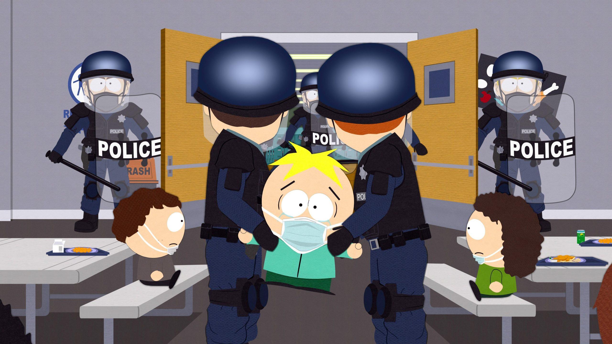 Cena da série South Park. Na animação, há um personagem sendo levado por dois policiais brancos. Ele também é branco, possui cabelos amarelos, usa máscara de cor azul claro, veste uma blusa ciano e uma calça verde. Eles estão em um refeitório, e os policiais vestem roupa azul, capacete azul, colete na cor preta, cinto na cor preta e joelheiras na cor preta.