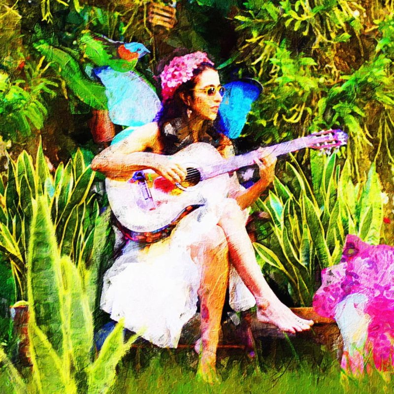 Capa do clipe A Lingua dos Animais. Ao centro há um desenho de Marisa Monte. Um mulher branca, de cabelos grandes, ondulados e pretos. Ela está sentada de pernas cruzadas. Veste um vestido branco e em seu colo há um violão. Ela tem asas de borboleta azul e coroa e flores em sua cabeça. O fundo é verde preenchido por espadas de São Jorge.