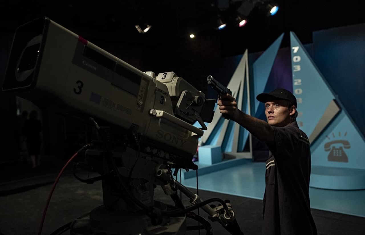 Cena do filme Interrompemos a Programação. Na imagem, o protagonista Sebastian, um homem branco loiro de olhos azuis, usa boné azul marinho, camiseta marrom e camisa cinza escura por cima. Ele aponta uma arma para uma câmera Sony de estúdio antiga. O fundo é um set de filmagem azul, preparado para o ano novo.
